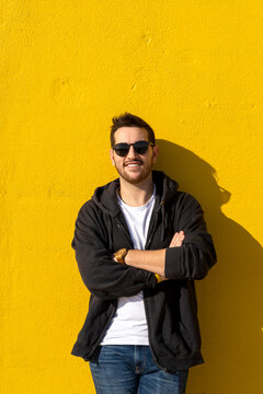 Young bearded man standing against a yellow wall with crossed arms