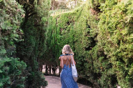 Woman walking through a maze of bushes