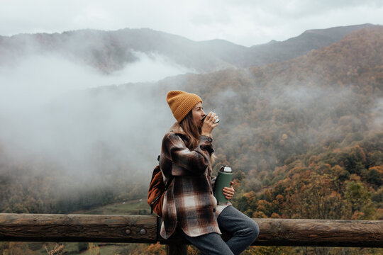 Portrait of woman traveling and exploring nature, preparing tea in a high place.