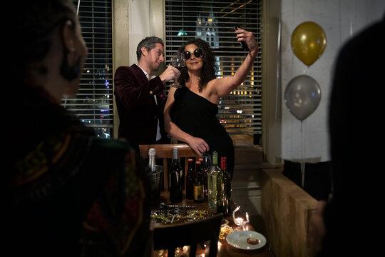 NYE: Woman Having Fun Taking Selfies At Party With Partner