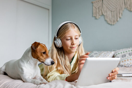 Child using tablet with dog on the bad