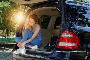 Sport woman jogger, tying shoes getting ready for workout outdoor sitting in car trunk