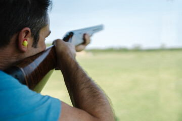 Mid Adult Man Training His Aim and Concentration Using a Shotgun in a Clay Pigeon Shooting Field Sport Centre