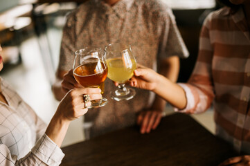 Friends toasting craft beers during happy hour