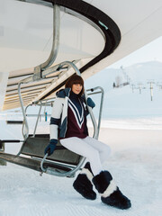 Stylish skier sits on chair lift.