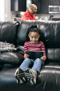 Home: Girl Using Tablet To Watch Videos While Dad Works From Hom