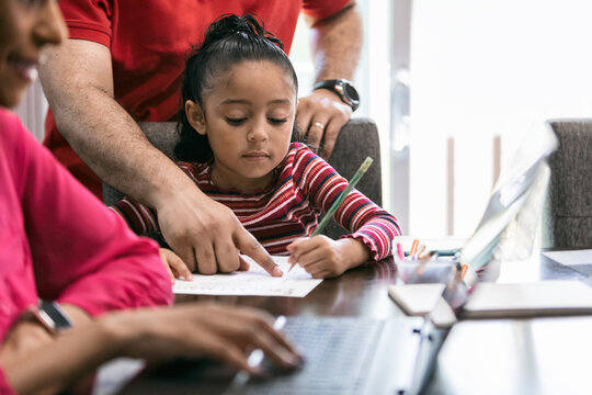 Home: Father Helps Girl With Homework While Mother Works Remotel