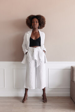 Studio fashion portrait of young african american woman posing in white linen suit. Afro hairstyle.