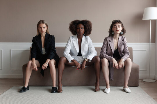 A small group of fashion multiracial multiethnic young beautiful sensual models are sitting in luxury room on sofa