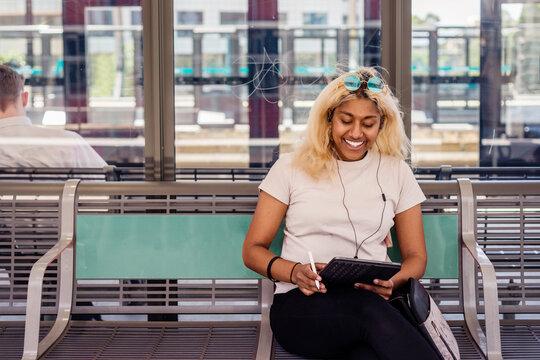 happy woman using ipad at train station