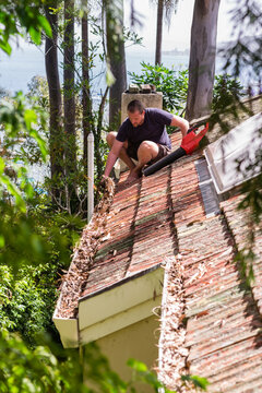 man clearing leaves off roof