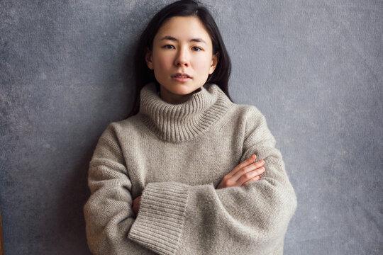 Winter style portrait of brunette asian woman posing indoor in big cozy warm sweater