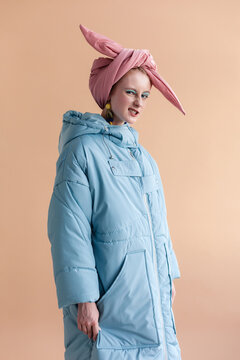 Fashion style studio portraits of beautiful woman posing in winter vogue stylish design coats on creamy pastel background.