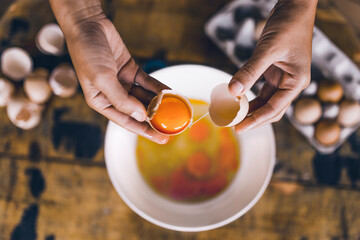 A flat lay picture of human hands cracking eggs in a wooden background.