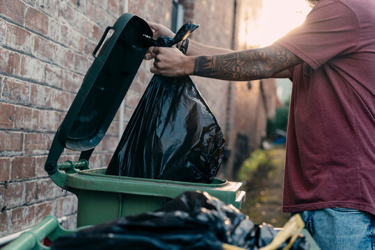 A close up picture of a young male hand throwing rubbish to the bin at the street.