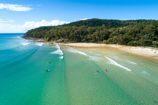 Surfers and others enjoying surf at Noosa.