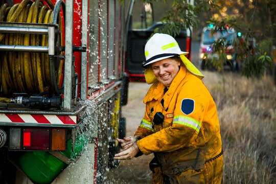 Female firefighter laughing and washing her hands beside firetruck