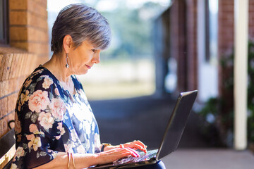 Older woman typing on laptop sitting outside