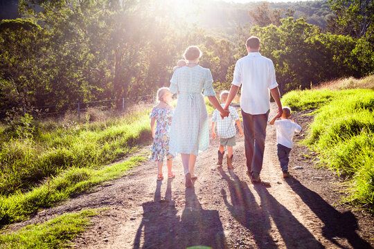 Rear view of family walking on dirt road passing through farm