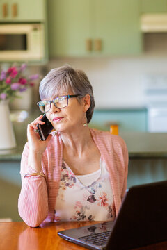 Mature woman on laptop at home using mobile phone to call for tech support