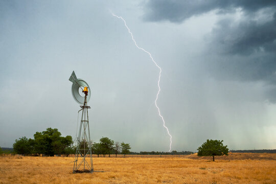 Lightning strikes ahead of a thunderstorm on farmland