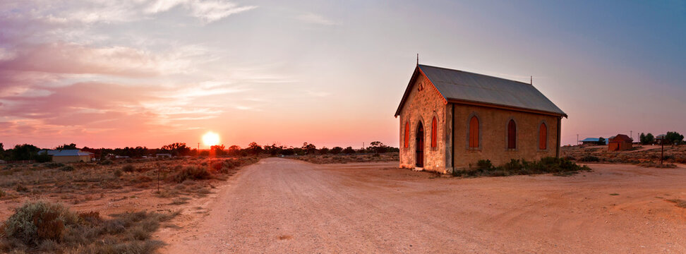 An isolated chapel beside a dirt road as the sun rises