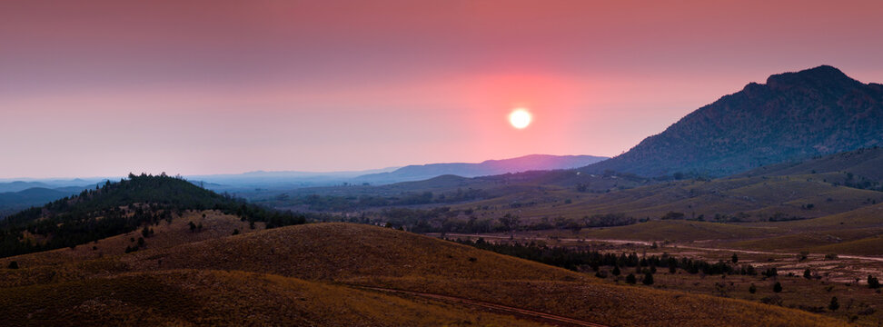 The Sun rising through heavy smoke haze over mountains of the Flinders Ranges