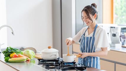 Fototapeta キッチンで料理をする女性 obraz