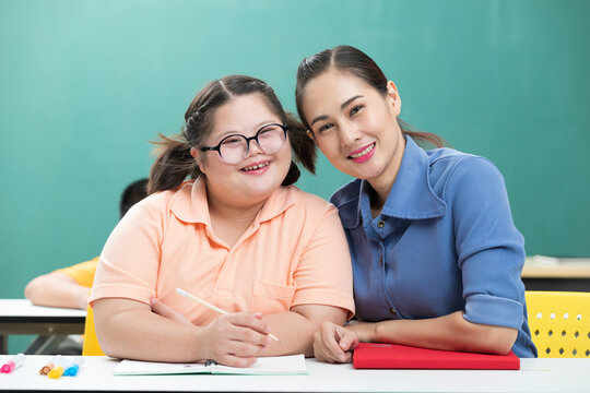 portrait asian disabled child or down syndrome child and woman teacher helping in classroom