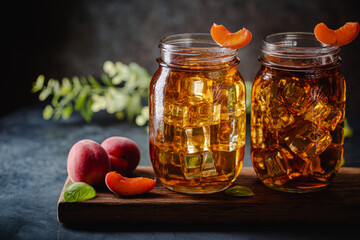 Glass of peach or apricot iced tea with fruit slices against dark blue background