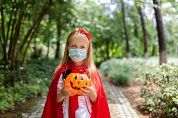 Portrait of cute Little Girl in costume of red hat in the park. Happy Halloween during coronavirus covid-19 pandemic quarantine concept. Kid wearing medical mask