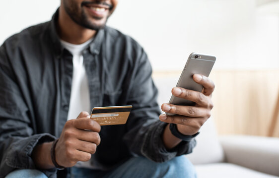 Man holding credit card and using smartphone at home, businessman shopping online, e-commerce, internet banking, spending money, working from home concept