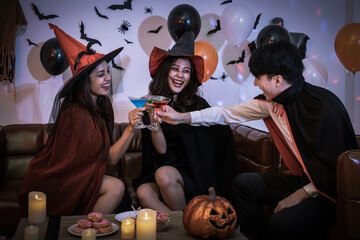 Young happy Asian people dressing Halloween costume, vampire and witch, celebrating in party. Holding and clinking wine glass.