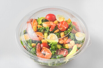 Plastic package with healthy shrimp caesar salad with avocado , kale, tomatoes and eggs to take...