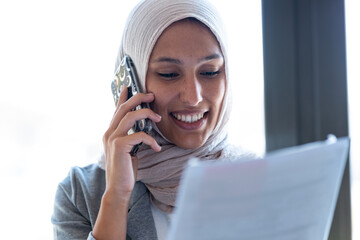 Beautiful young muslim business woman wearing hijab talking with her smart phone while holding papers looking through the window in the office.