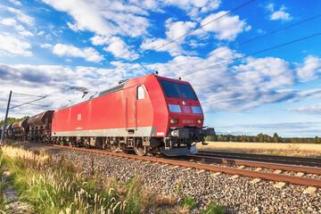 Eine Elektrolokomotive der Baureihe 185 der DB Cargo vor einem Güterzug