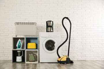 Modern vacuum cleaner and different household appliances near white brick wall indoors