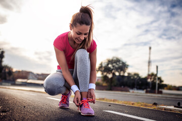Runner tying jogging shoes.