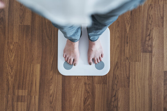 Top view, woman standing on body scale, checking body weight, dieting, lose and gain weight concept
