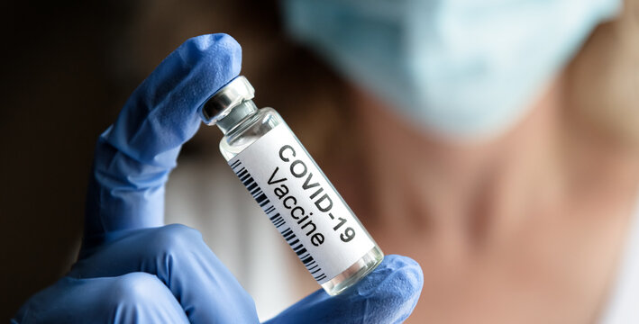 COVID-19 vaccine concept, female doctor holds coronavirus medication in office or laboratory