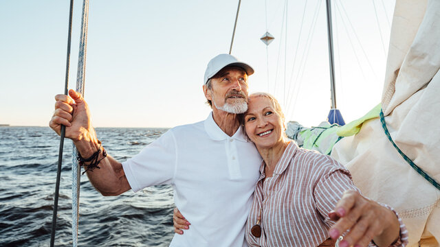 Portrait of a beautiful mature couple standing on a sailboat enjoying a vacation and looking away