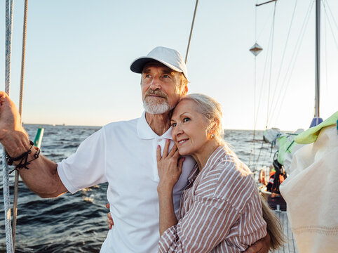 Affectionate senior couple embracing on yacht and looking into the distance. Retired couple standing together on sailboat.