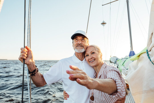 Happy mature woman pointing into the distance while embracing by his husband on their yacht