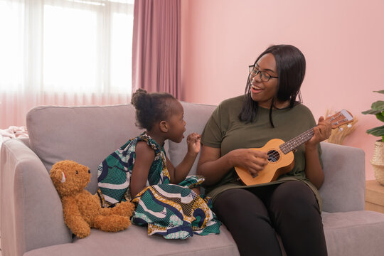 Portrait of smiling business black African american woman, a mom with her daughter playing an ukulele music in family relationship concept on pink background. A black kid toddler girl with her parent.