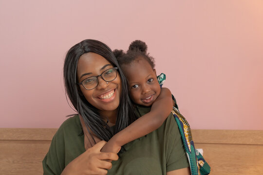 Portrait of smiling business black African american woman, a mom with her daughter working from home in family relationship concept on pink background. A black kid toddler girl with her parent.
