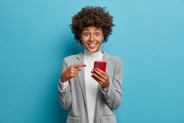 Joyful surprised woman employee opens calendar on mobile phone for planning appointment, points at smartphone display and wears formal outfit. Female office worker happy to check balance on salary day