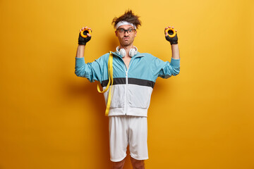 Indoor shot of serious man goes in for sport regularly and squeezes round expander, wears headphones on neck. Motivated sportsman gains muscles, stands against yellow background. Sporty athletic guy