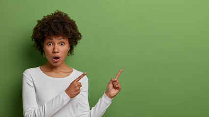 Stupefied dark skinned Afro American woman with curly hair has widely opened mouth, wears casual white clothes and demonstrates blank space against green studio background. Follow this direction