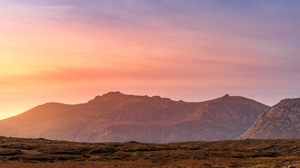 Dramatic sunset at mountain range. Setting sun highlighting Mourne Mountains, County Down, Northern Ireland