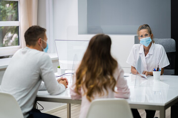 Doctor Talking To Patient At Meeting About Pregnancy